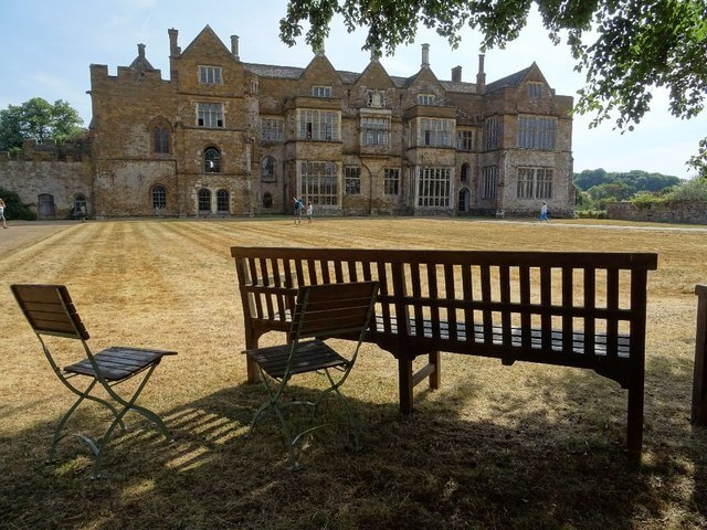 A photograph of Broughton Castle with a bench and chairs in the foreground