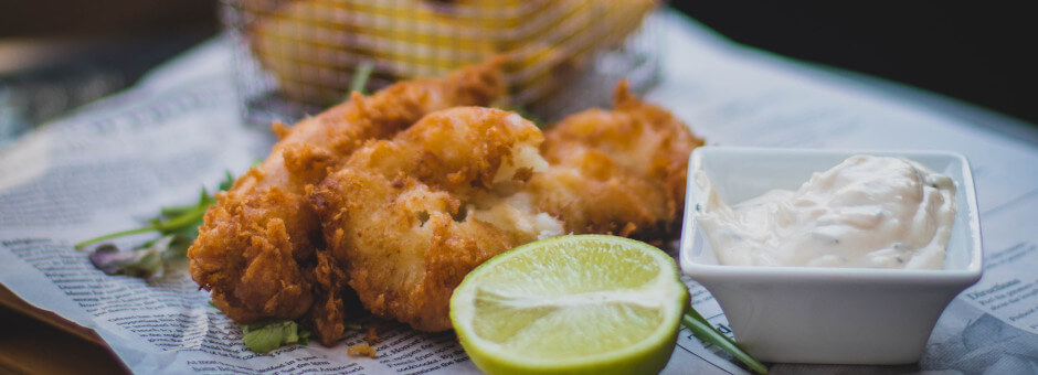 Fresh looking fish and chips with tartar sauce and slice of lime