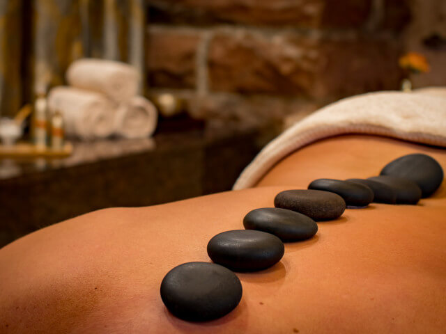 Lady relaxing with a stone treatment in a spa