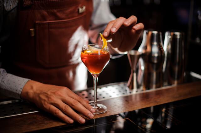 Barman making a cocktail at a bar in Bath