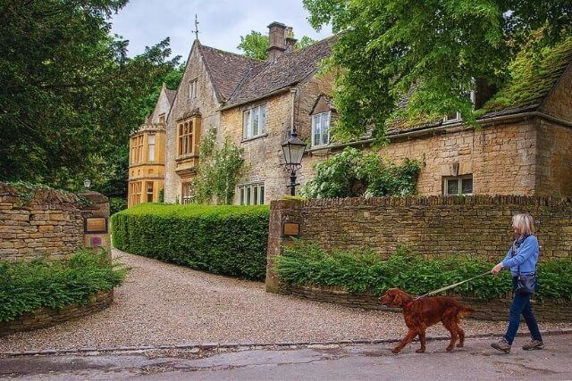 Woman walking dog outside of The Atrium in Upper Slaughter